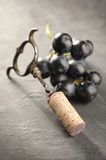 Cork, corkscrew and red grapes Stock Images