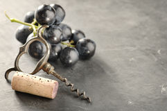 Cork, corkscrew and red grapes. Cork,corkscrew and red grapes on gray background Royalty Free Stock Image