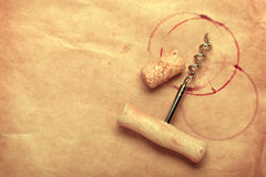 Cork and corkscrew with red wine stains. On brown paper background with copy space Royalty Free Stock Photography