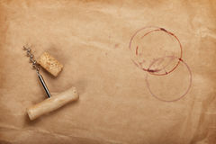 Cork and corkscrew with red wine stains. On brown paper background with copy space Stock Photography
