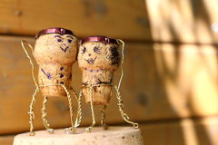 Cork figures. Man and woman cork figures in mini metal chairs royalty free stock photo