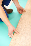 Cork flooring work. Close-up process of cork boards laying during indoors flooring work Royalty Free Stock Images