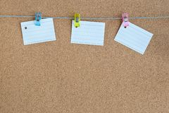 Cork memory board with blank peaces of paper hanging on rope with clothes pin, horizontal. Cork memory board with blank peaces of paper hanging on the rope with stock photo