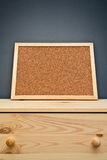 Cork memory board on wooden cabinet Royalty Free Stock Image