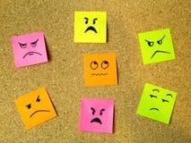 cork raad met kleurrijke post-its die diverse emoticons met communicatie van de woedeemotie het beschuldigen concept vertegenwoor stock foto's