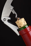 Cork-screw. Opening wine bottle over black background Royalty Free Stock Image