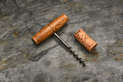 Cork Screw and Cork. Top view of an old fashioned cork screw and cork on a slate background Royalty Free Stock Photos