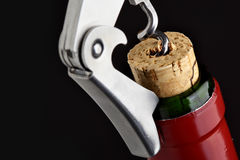 Cork-screw open wine bottle. Over black background Stock Image