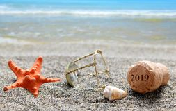 Cork stopper of champagne with number 2019 and seashell with starfish on sand beach. royalty free stock images