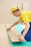 Cork worker at flooring work. One carpenter worker laying cork boards during indoors flooring work Royalty Free Stock Image