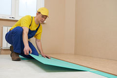Cork worker at flooring work. One carpenter worker laying cork boards during indoors flooring work Stock Photography