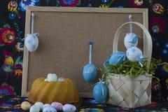 Διακόσμηση Πάσχας με τα άσπρα και μπλε αυγά στο χρωματισμένο υφαντικό υπόβαθρο με το corkboard στοκ εικόνα με δικαίωμα ελεύθερης χρήσης