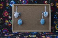Διακόσμηση Πάσχας με τα άσπρα και μπλε αυγά στο χρωματισμένο υφαντικό υπόβαθρο με το corkboard στοκ εικόνα