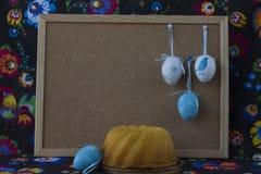 Διακόσμηση Πάσχας με τα άσπρα και μπλε αυγά στο χρωματισμένο υφαντικό υπόβαθρο με το corkboard στοκ εικόνες με δικαίωμα ελεύθερης χρήσης