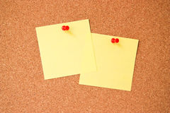 Corkboard. Two yellow post-it notes with red pushpins on corkboard Stock Image