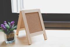 Corkboard, artificial flower in small glass pot on a wooden tabl. Blank corkboard, purple artificial flower in small glass pot on a wooden desk beside window Royalty Free Stock Images