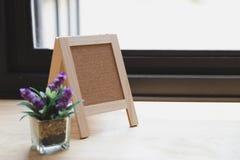 Corkboard, artificial flower in small glass pot on a wooden tabl. Blank corkboard, purple artificial flower in small glass pot on a wooden desk beside window Stock Photos