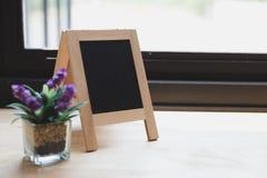 Corkboard, artificial flower in small glass pot on a wooden tabl. Blank corkboard, purple artificial flower in small glass pot on a wooden desk beside window Royalty Free Stock Image