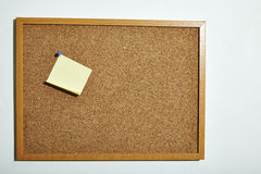 Corkboard. Blank yellow paper note with blue pin on corkboard royalty free stock photography