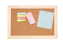 Corkboard with empty blue pink and yellow notes Royalty Free Stock Images