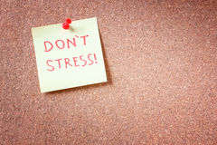 Corkboard with pinned yellow note and the phrase dont stress written on it. room for text. Corkboard with pinned yellow note and the phrase dont stress written Royalty Free Stock Photo