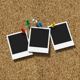 Corkboard with pushpins and three polaroid prints Stock Photography
