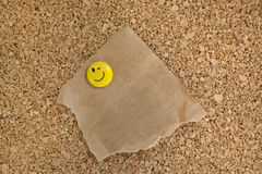 Corkboard with torn paper bag attached Stock Image