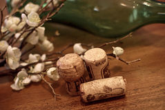 Corks. A stil life of some corks in front of a green bottle and some flowers Royalty Free Stock Images