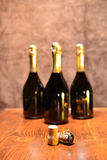 Corks and bottles. Two corks on a wooden table and four full bottles of wine on the background Royalty Free Stock Image