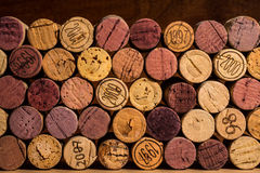 Corks are stacked against a dark wood background Stock Photo
