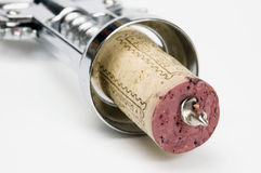 Corkscrew. A corkscrew piercing a red wine cork on a white background Stock Image