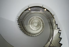 Corkscrew. Spiral stair in white with metal banister rail Stock Image