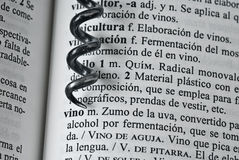 Corkscrew. Part of a corkscrew over the definition of the word vino Stock Photography