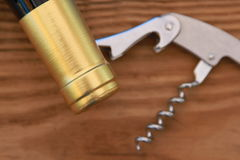 Corkscrew and Bottleneck on wooden Background. Metal Corkscrew and Bottleneck on Wooden Background Close-up royalty free stock photo