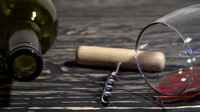 Corkscrew, cork, bottle and glass of red wine on a wooden table. Corkscrew, cork, bottle and glass of red wine on a wooden background stock video