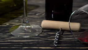 Corkscrew, cork, bottle and glass of red wine on a wooden table. Corkscrew, cork, bottle and glass of red wine on a wooden background stock video footage