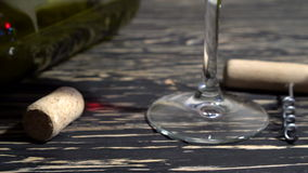 Corkscrew, cork, bottle and glass of red wine on a wooden table. Corkscrew, cork, bottle and glass of red wine on a wooden background stock footage