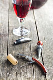 Corkscrew and cork. Corkscrew and cork on wooden table stock images