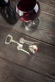 Corkscrew e um vidro do vinho em uma tabela de madeira velha Imagens de Stock