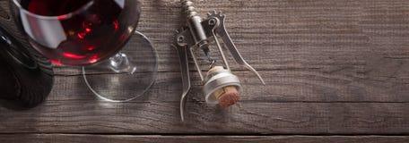 Corkscrew e um vidro do vinho em uma tabela de madeira velha Imagem de Stock Royalty Free