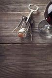 Corkscrew e um vidro do vinho na tabela de madeira velha Fotos de Stock Royalty Free