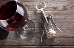 Corkscrew e um vidro do vinho na tabela de madeira velha Imagens de Stock Royalty Free