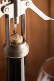 Corkscrew e um vidro do vinho na tabela de madeira velha Fotografia de Stock