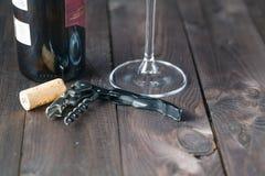 Corkscrew a garrafa e o vidro de vinho na tabela de madeira Foto de Stock Royalty Free