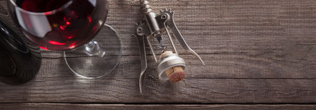 Corkscrew and a glass of wine on an old wooden table.  Royalty Free Stock Image