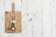 Corkscrew na rocznik tnącej desce nad białym drewnianym stołem w Fotografia Royalty Free