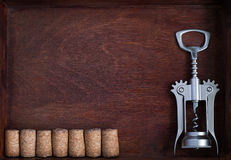 Corkscrew and a row of identical wine corks into dark box. Corkscrew and a row of identical wine corks into dark wood box royalty free stock images