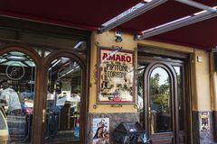 Entrance of a bar of Corleone in Sicily, Italy. Corleone, Italy - August 9, 2017: Entrance of a bar with people inside and a sign of the Amaro liquor in Corleone Royalty Free Stock Images