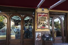 Entrance of a bar of Corleone in Sicily, Italy. Corleone, Italy - August 9, 2017: Entrance of a bar with people inside and a sign of the Amaro liquor in Corleone Royalty Free Stock Photo