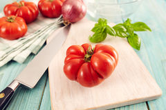 Corleone Tomato. Tomatoes corleone type for sauce on a aqua wooden table with basil and onion Stock Photography